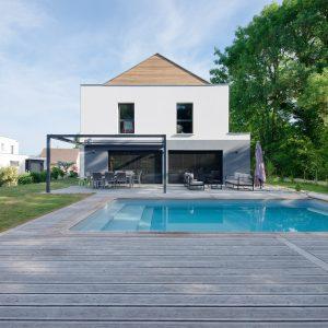 Construction à toiture audacieuse - façade arrière, piscine et terrasse