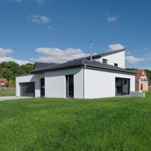 Construction à toiture audacieuse - façade avant, garage, flanc et jardin
